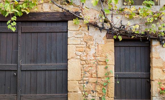 un mur en pierre et deux grandes portes en bois grises